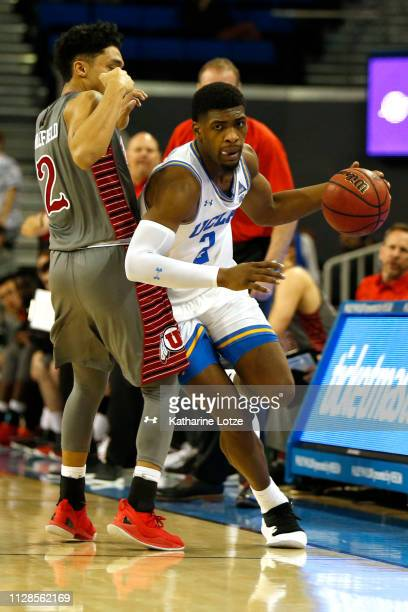 Cody Riley of the UCLA Bruins drives around Sedrick Barefield of the Utah Utes during the second half of a game at Pauley Pavilion on February 09...