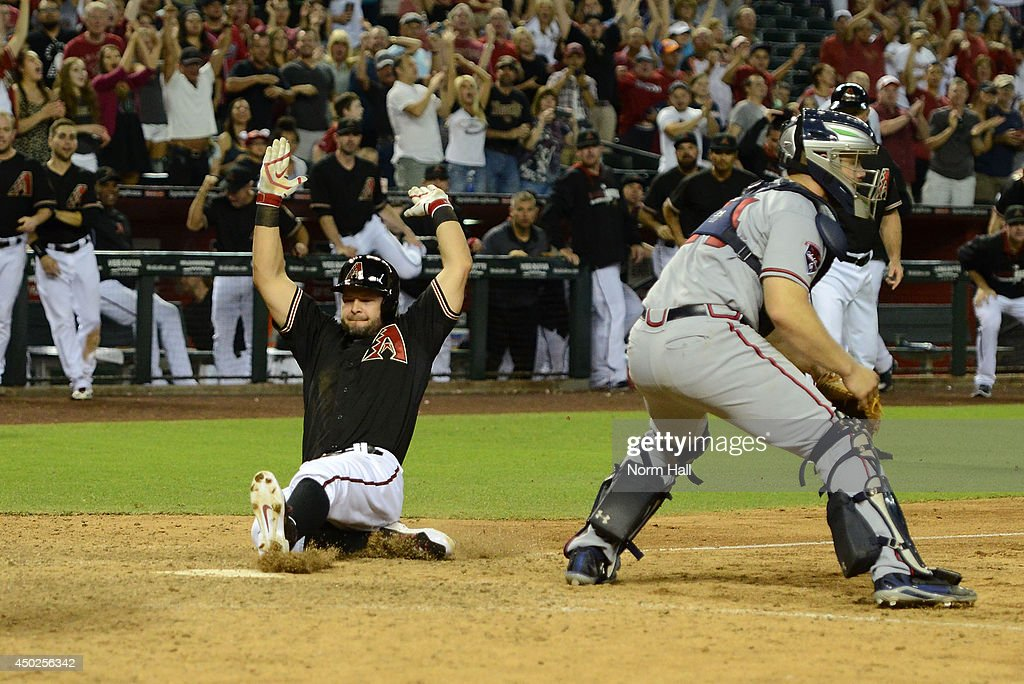 Cody Ross #7 of the Arizona Diamondbacks scores the winning run in the 11th inning on teammate Gerardo Parra's #8 hit against the Atlanta Braves at Chase Field on June 7, 2014 in Phoenix, Arizona. Arizona won 4-3.