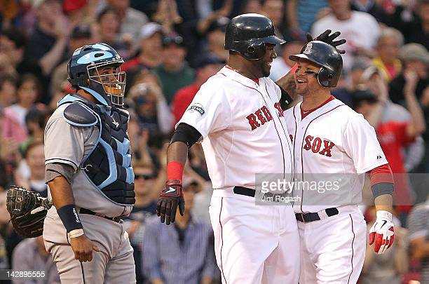 Cody Ross of the Boston Red Sox celebrates his home run with David Ortiz as Jose Molina of the Tampa Bay Rays looks on at Fenway Park April 14 2012...