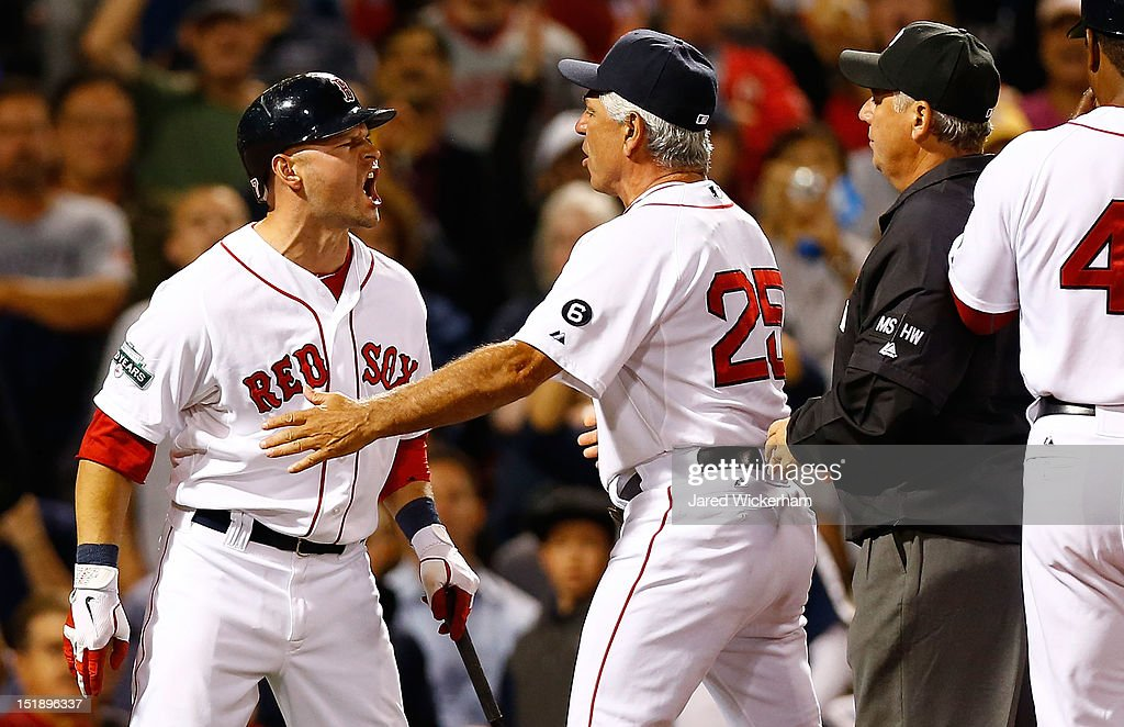 Cody Ross #7 of the Boston Red Sox is restrained by manager Bobby Valentine #25 while arguing a called three strike with home plate umpire Alfonso Marquez after being thrown out of the game against the New York Yankees during the game on September 12, 2012 at Fenway Park in Boston, Massachusetts.