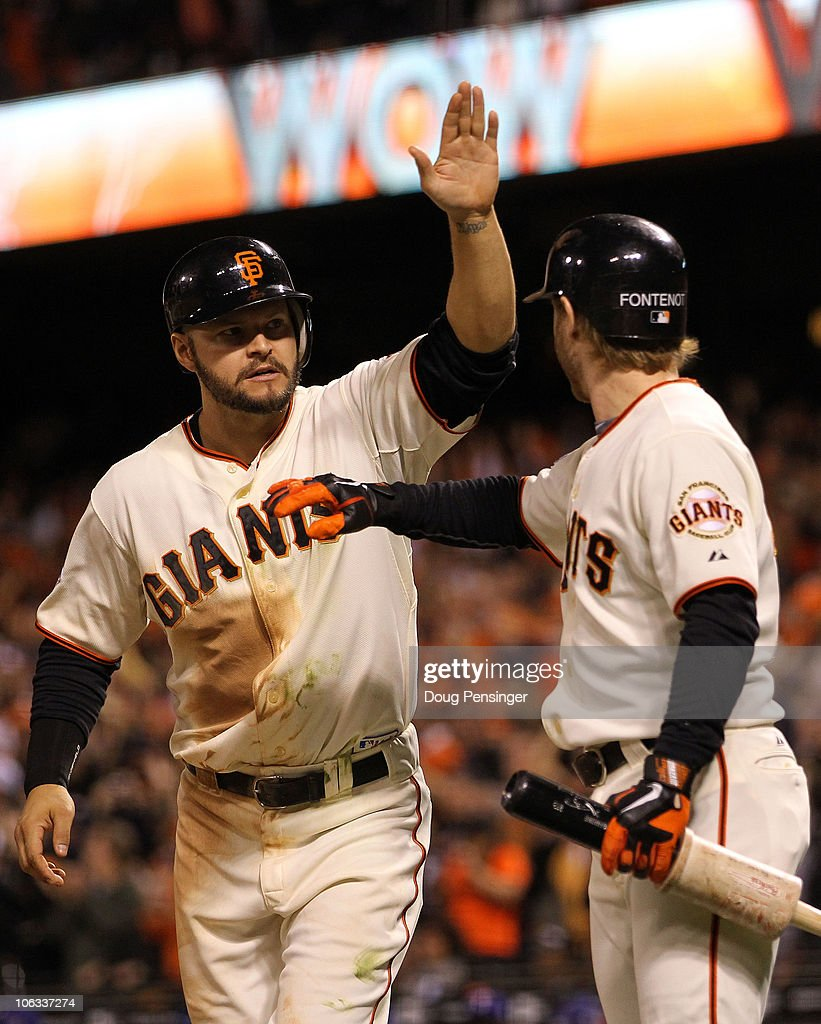 Cody Ross #13 of the San Francisco Giants celebrates scoring a run with teammate Mike Fontenot #14 in the eighth inning while taking on the Texas Rangers in Game Two of the 2010 MLB World Series at AT&T Park on October 28, 2010 in San Francisco, California.