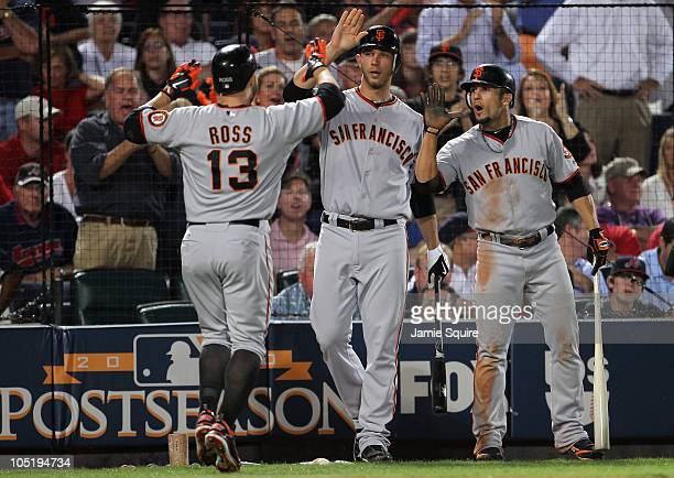 Cody Ross of the San Francisco Giants is congratulated by Madison Bumgerner and Andres Torres after hitting a home run during the 6th inning of Game...