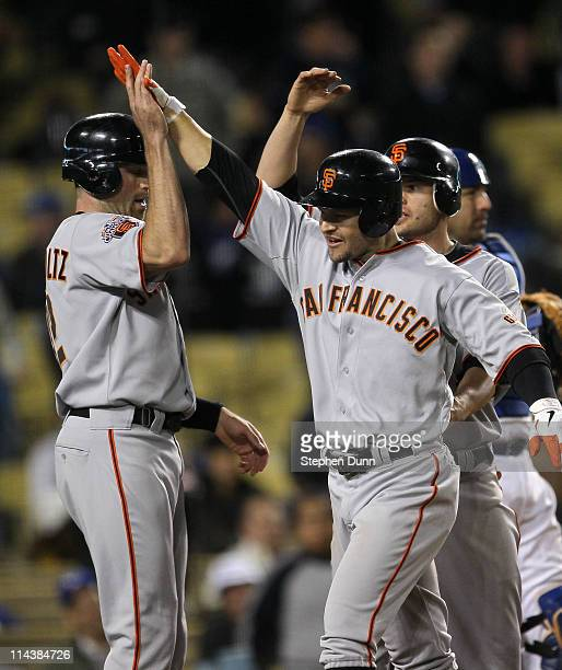 Cody Ross of the San Francisco Giants is greeted by Nate Schierholtz and Freddy Sanchez after hitting a three run home run in the ninth inning...