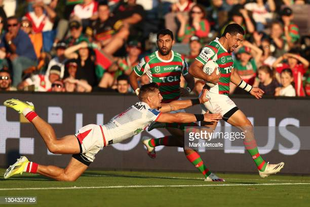 Cody Walker of the Rabbitohs evades the tackle of Zac Lomax of the Dragons to score a try during the Charity Shield & NRL Trial Match between the...