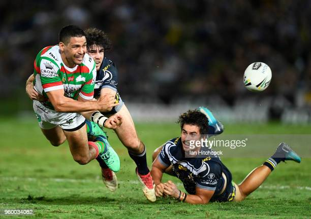 Cody Walker of the Rabbitohs gets a pass away despite the tackle of Jake Granville and Enari Tuala of the Cowboys during the round 11 NRL match...