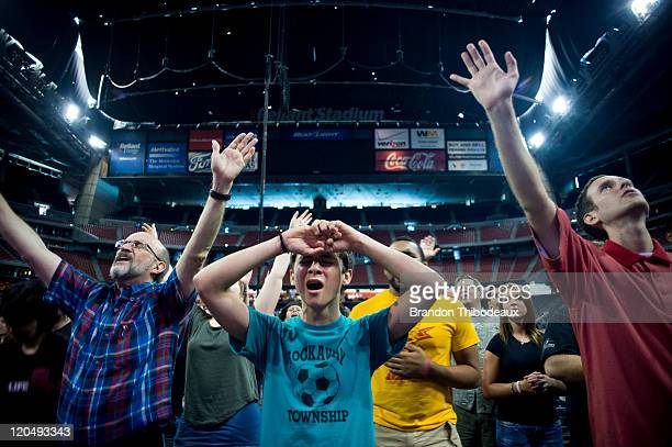 Cody Walsh stands with arms raised in a crowd of attendees as they dance and sing during the opening musical act of the nondenominational prayer and...