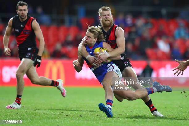 Cody Weightman of the Bulldogs is tackled by Michael Hurley of the Bombers during the round 7 AFL match between the Essendon Bombers and the Western...
