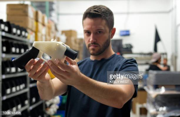 TOPSHOT Cody Wilson owner of Defense Distributed company holds a 3D printed gun called the 'Liberator' in his factory in Austin Texas on August 1...