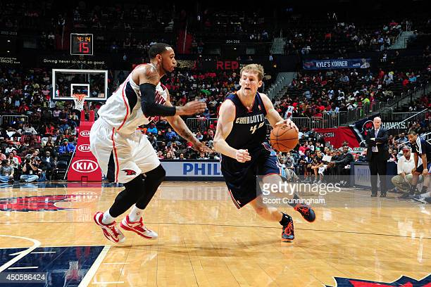 Cody Zeller of the Charlotte Bobcats drives to the basket against Mike Scott of the Atlanta Hawks on April 14 2014 at Philips Arena in Atlanta...