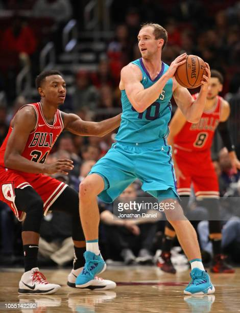 Cody Zeller of the Charlotte Hornets looks to pass under pressure from Wendell Carter Jr #34 of the Chicago Bulls at the United Center on October 24...