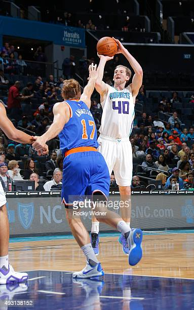 Cody Zeller of the Charlotte Hornets shoots a three pointer against Lou Amundson of the New York Knicks on October 17 2015 at Time Warner Cable Arena...