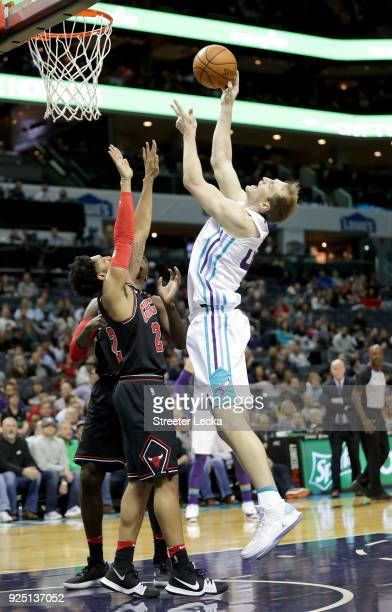 Cody Zeller of the Charlotte Hornets shoots over Cameron Payne of the Chicago Bulls during their game at Spectrum Center on February 27 2018 in...