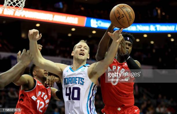 Cody Zeller of the Charlotte Hornets tries to grab the ball from teammates Oshae Brissett and Terence Davis of the Toronto Raptors during their game...