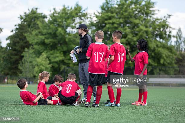co-ed diverse childrens soccer team midfield with coach - amateur stock pictures, royalty-free photos & images