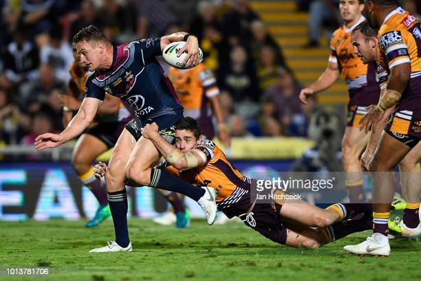 Coen Hess of the Cowboys is tackled by Andrew McCullough of the Broncos during the round 22 NRL match between the North Queensland Cowboys and the...