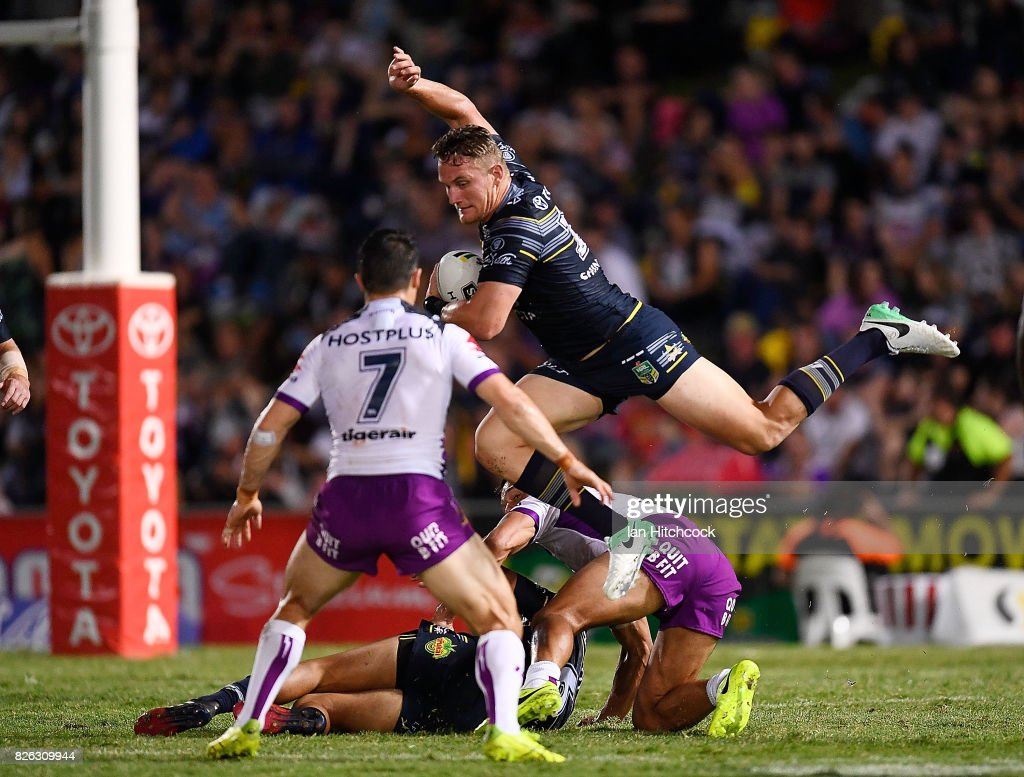 Coen Hess of the Cowboys jumps over Will Chambers of the Storm and is then tackled by Cooper Cronk of the Storm during the round 22 NRL match between the North Queensland Cowboys and the Melbourne Storm at 1300SMILES Stadium on August 4, 2017 in Townsville, Australia.