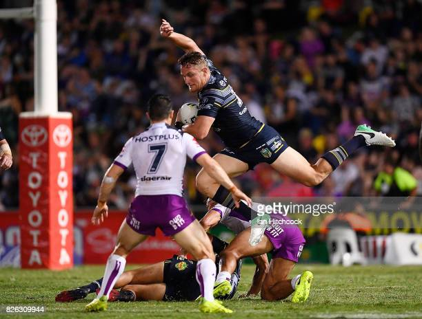 Coen Hess of the Cowboys jumps over Will Chambers of the Storm and is then tackled by Cooper Cronk of the Storm during the round 22 NRL match between...