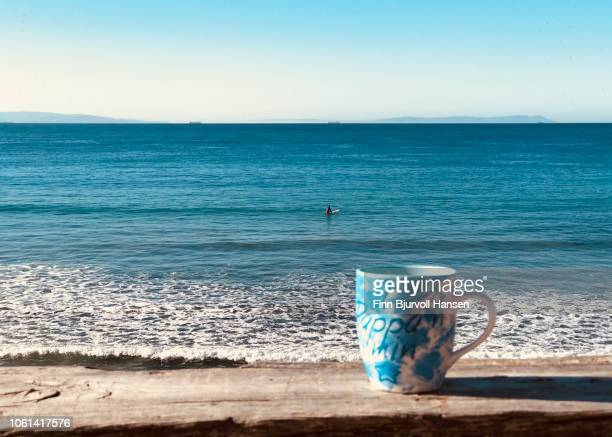 coffecup on e wooden fence in front of the atlantic ocean. a surfer in the background waiting for waves - finn bjurvoll stock photos and pictures