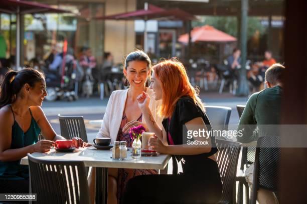 caffè e un mettersi al passo al sole - amicizia tra donne foto e immagini stock