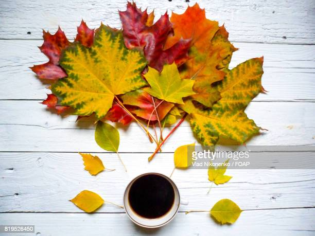 Coffee and autumn leaves on wooden table