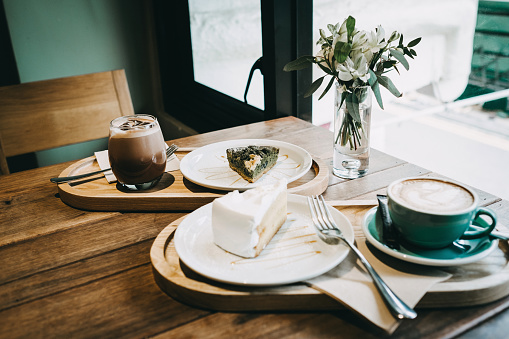 Coffee and cakes served on table in cafe by the window - gettyimageskorea