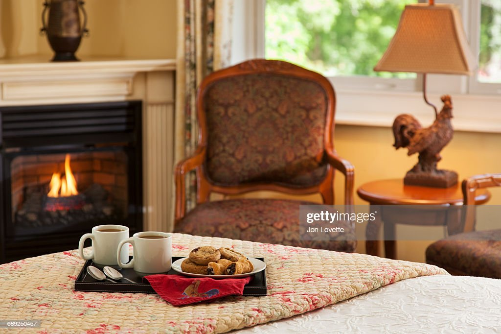 Coffee and cookies on bed by fire : Stock Photo
