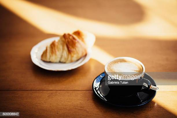 Coffee and croissant on a table.