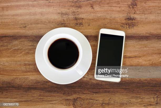 coffee and smart phone on wooden desk - wood table top stock photos and pictures