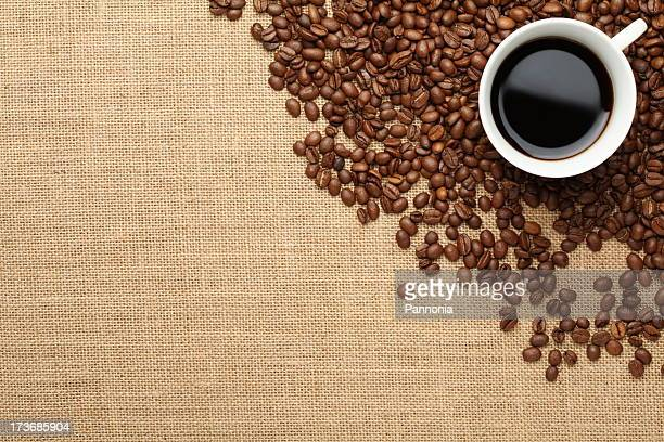 Coffee beans and coffee in mug background