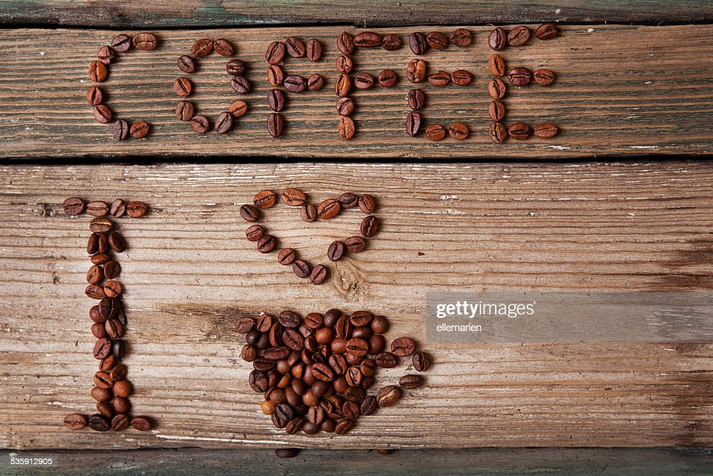 coffee beans and cup with heart on wooden background : Stock Photo