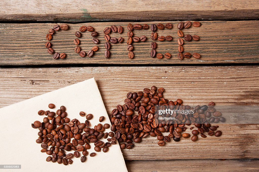coffee beans and napkin on wooden background : Stock Photo