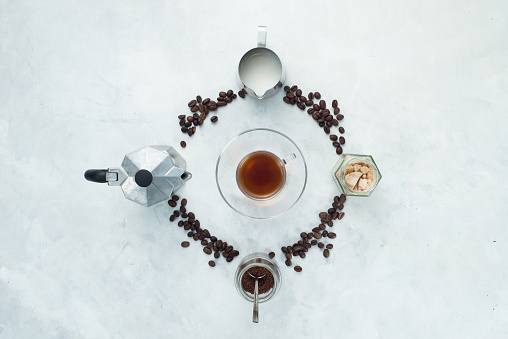 Coffee beans circle with moka pot, espresso cup, milk jug, ground coffee and sugar. Clock dial... - gettyimageskorea