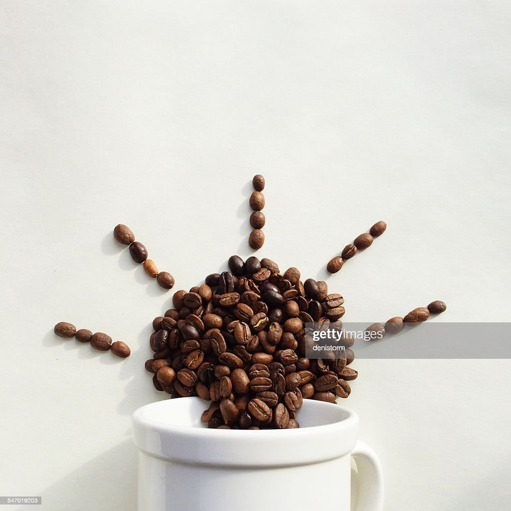 Coffee beans coming out of a cup in the shape of the sun : Stock Photo