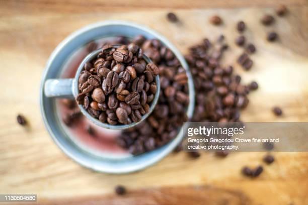 coffee beans in a coffee cup - gregoria gregoriou crowe fine art and creative photography. fotografías e imágenes de stock