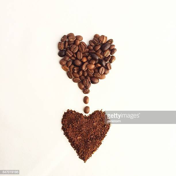 Coffee beans in a heart shape, dripping into another heart shape of ground coffee