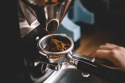 Coffee beans in a portafilter by the coffee grinder 618340264