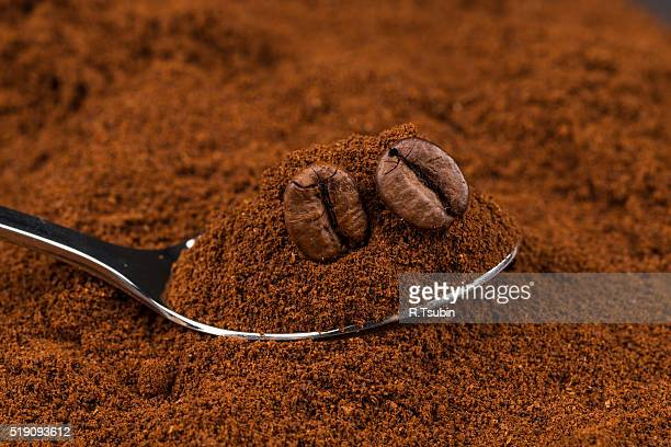 Coffee beans on heap of ground coffee