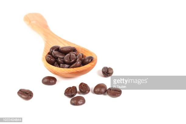 coffee beans on wood spoon, isolated on wooden board - mocha stock photos and pictures