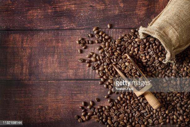 coffee beans roasted in a sack with scoop on wooden table background - caffeine stock pictures, royalty-free photos & images