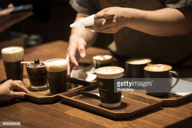 Coffee beverages are served on trays inside the Starbucks Corp Reserve Roastery store in Shanghai China on Friday May 11 2018 Starbucksis laying out...