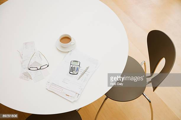 Coffee, bills and calculator on table