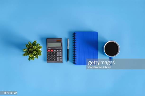 coffee break. calculator and notebook on blue desk. - grupo de objetos imagens e fotografias de stock