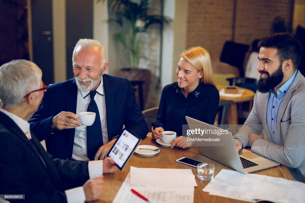 Coffee break while discussing business plan at cafe. : Stock Photo