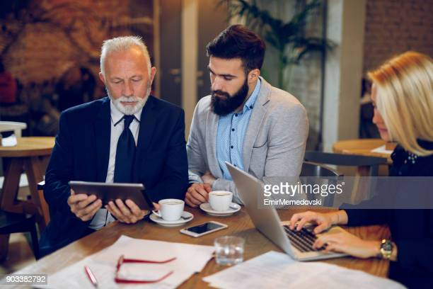 coffee break while discussing business plan at cafe - emir memedovski stock pictures, royalty-free photos & images
