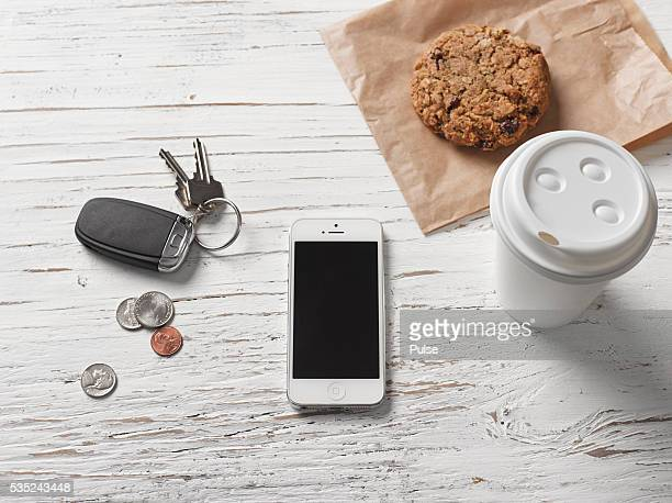 Coffee, cookie, car key, coins and smartphone on white table