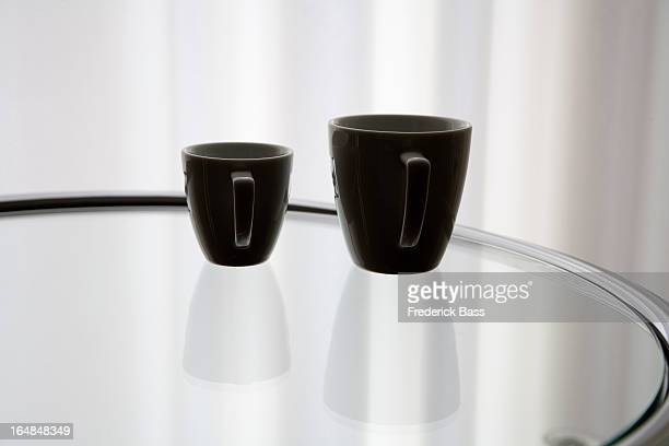 A coffee cup and an espresso cup reflected on a glass table