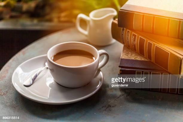 Café Copa y libros sobre una mesa de madera