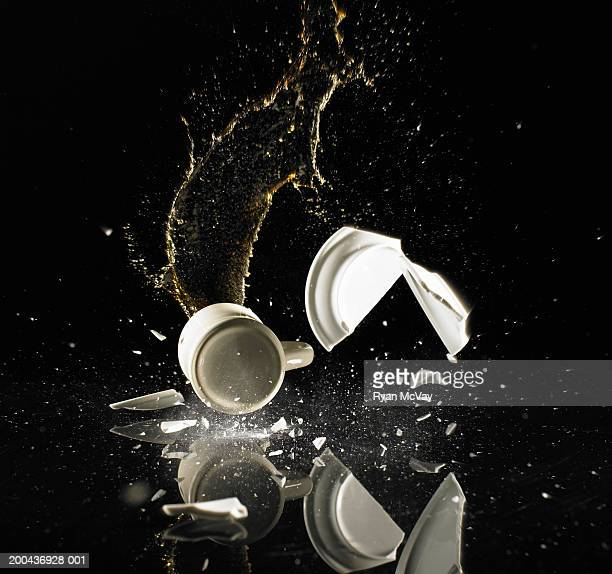 Coffee cup and saucer shattering on floor