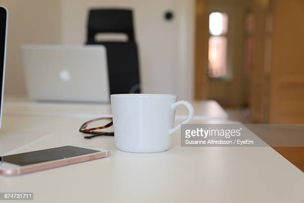 Coffee Cup And Smart Phone On Table In Office