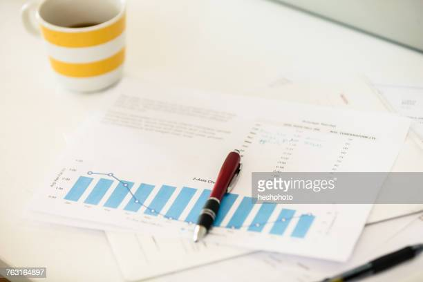 coffee cup, bar chart and pen on office desk - heshphoto stock pictures, royalty-free photos & images